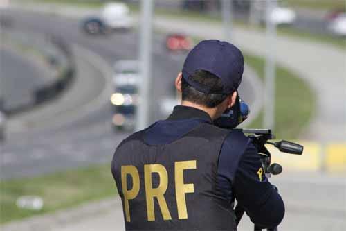 Foto de policial da PRF em serviço com uso de radar móvel na BR