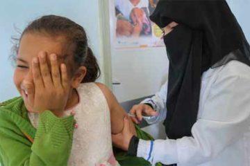 Foto de criança sendo vacinada, na Síria
